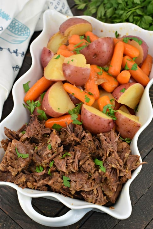 White scalloped dish with pot roast, potatoes and carrots