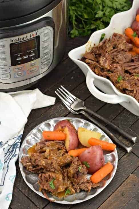 Plate of pot roast, carrots and potatoes with Instant Pot in background