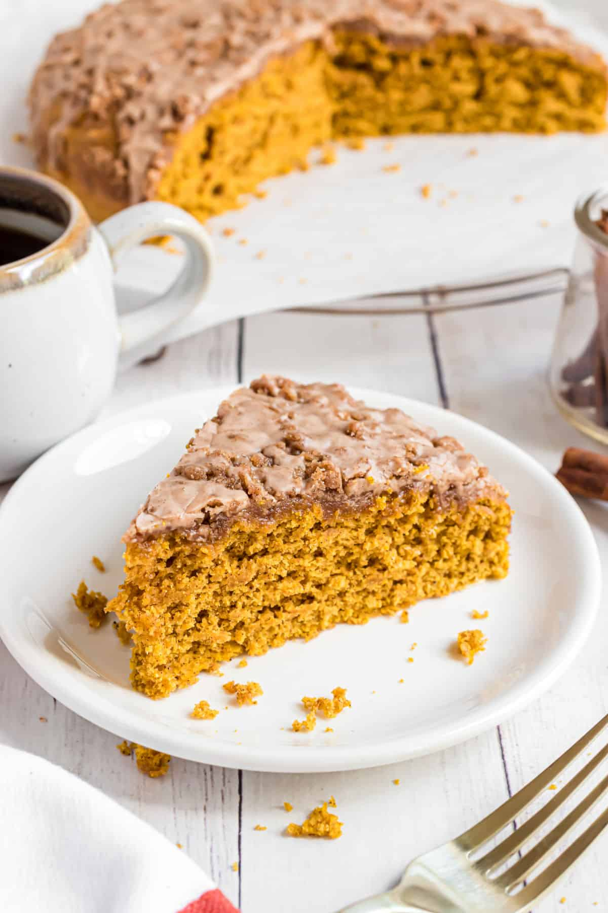 Slice of pumpkin coffee cake served on a white plate.