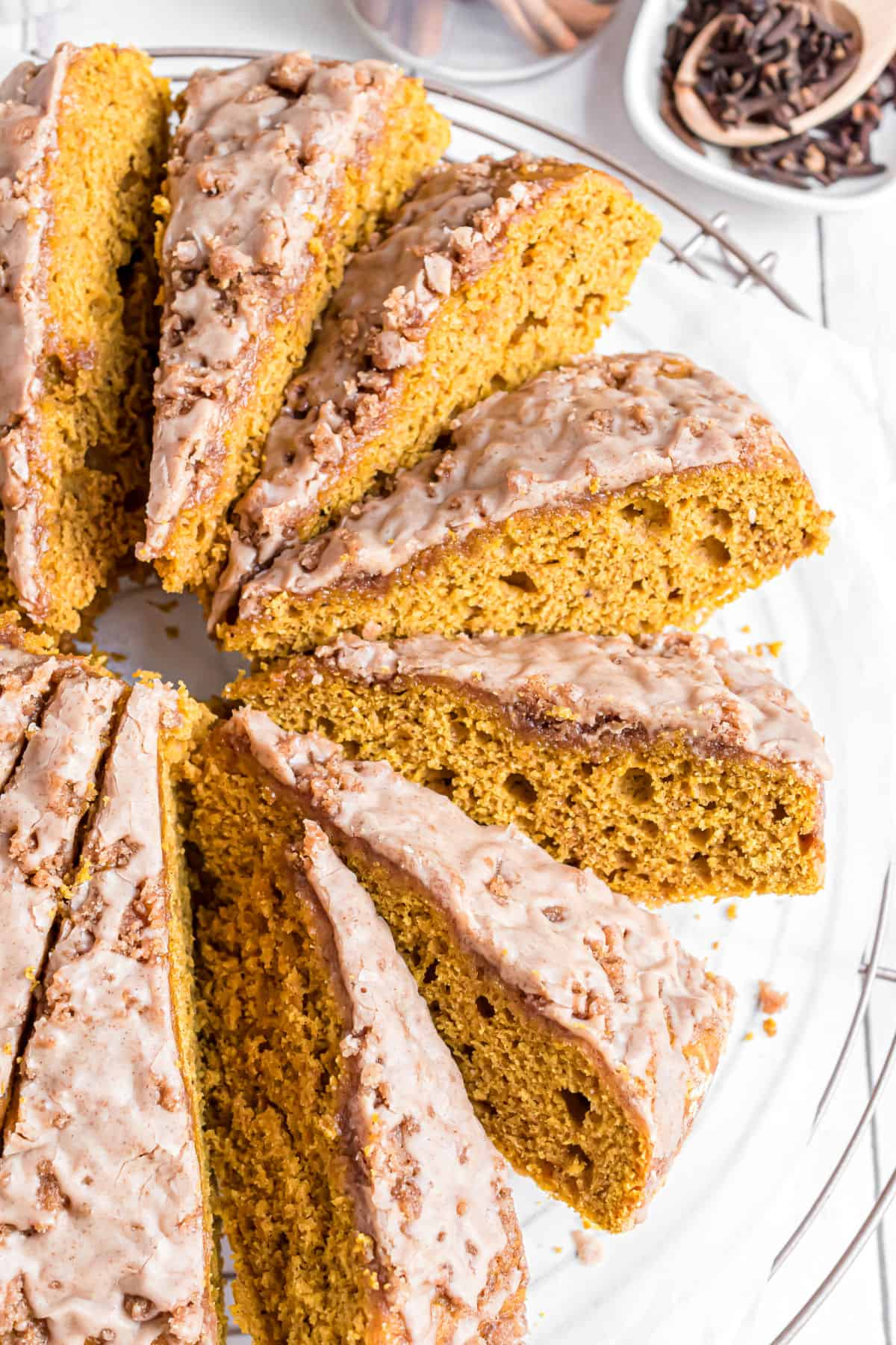 Pumpkin coffee cake with streusel and icing, sliced on a plate.