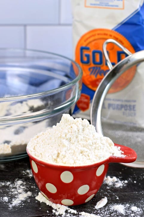 Bag of flour with red and white polkadot measuring cup of flour.