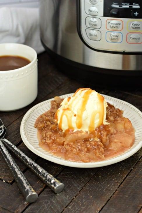 Apple crisp on dessert plate with ice cream and caramel.