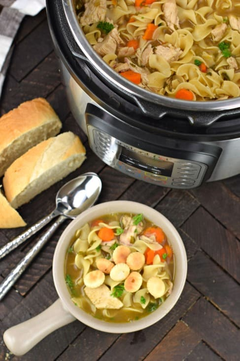 Bowl of chicken noodle soup being served from the instant pot.