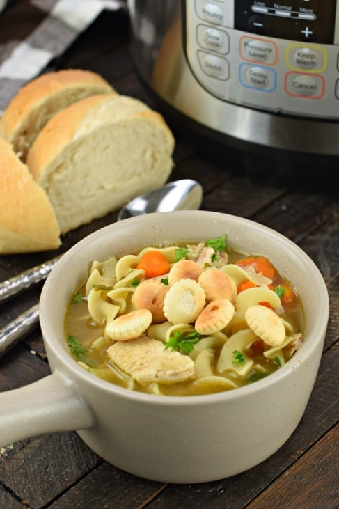White soup bowl with handle filled with chicken noodle soup and oyster crackers.
