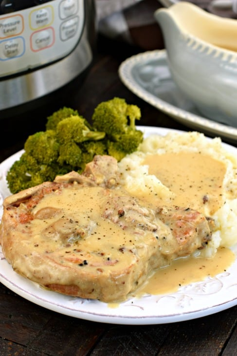 Pork chop and mashed potatoes covered in mushroom gravy on a white plate with a side of steamed broccoli.