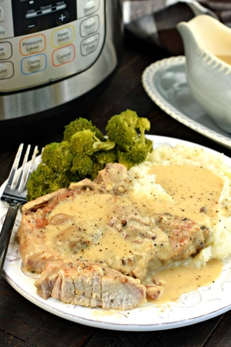 Pork chop with a piece cut to see the tender inside. Topped with mushroom gravy on a white plate and pressure cooker in background.