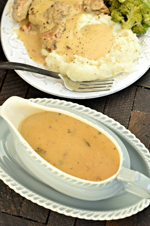 Gray gravy bowl filled with mushroom gravy with a white plate topped with mashed potatoes and pork chops in background.