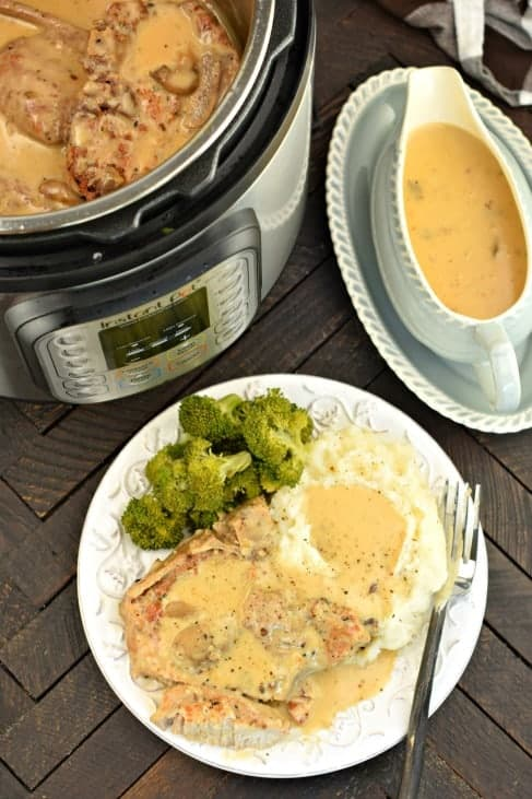 Pork chops, mashed potatoes and broccoli covered in mushroom gravy on a white plate. Gravy bowl and Instant Pot in background.