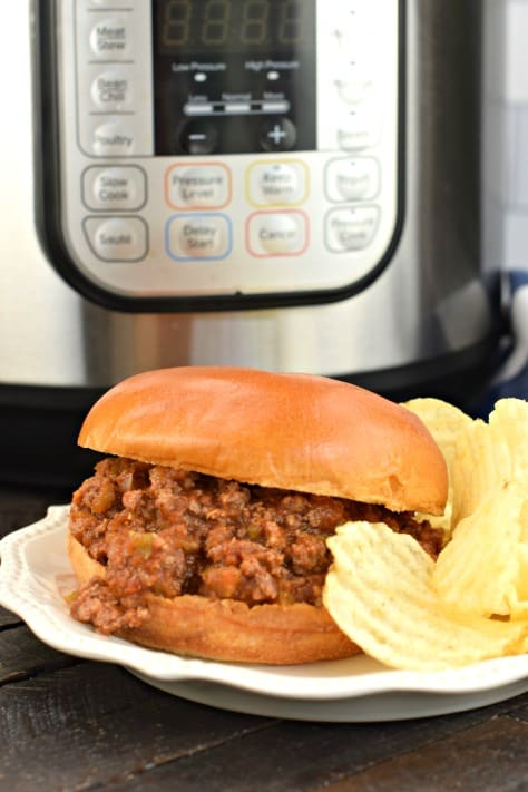 Bun with sloppy joes and potato chips. Instant Pot in background.