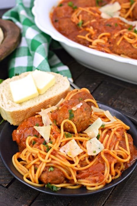 Plate with spaghetti, meatballs, and french bread.