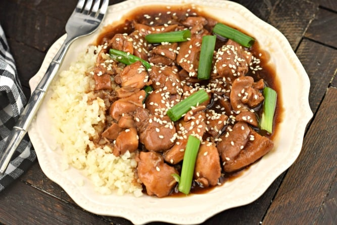 Mongolian chicken garnished with sesame seeds and served with rice.
