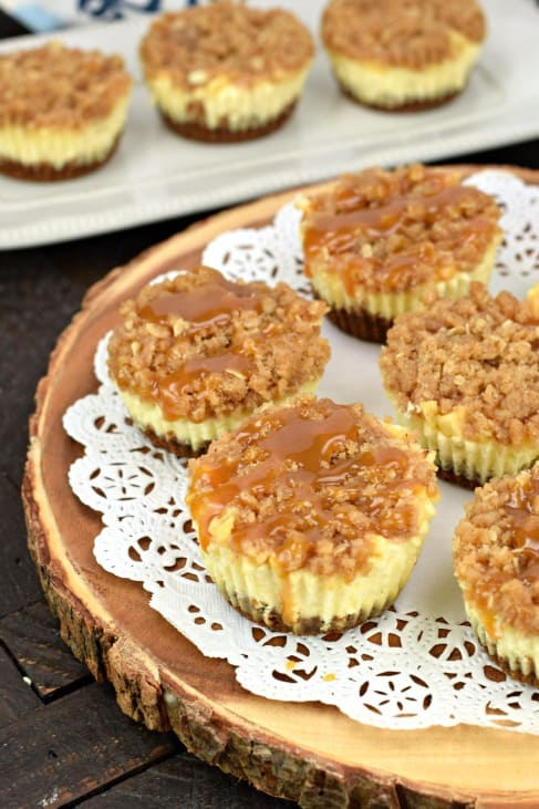 Caramel apple cheesecakes on a white doily on a wooden cake plate.