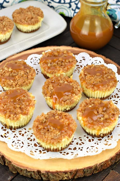 Caramel apple cheesecakes on a wooden cake plate with white doily.