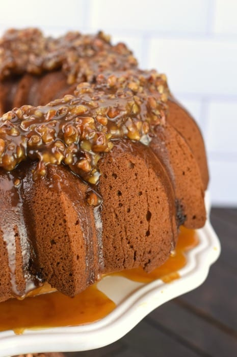 Bundt cake with pecan pie topping and swirl with caramel sauce.