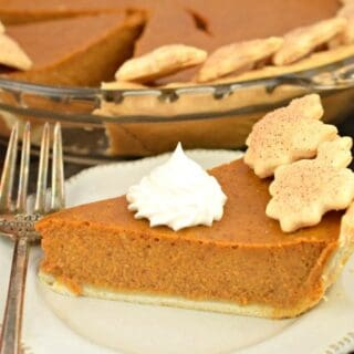 Slice of pumpkin pie with dollop of whipped cream on top.