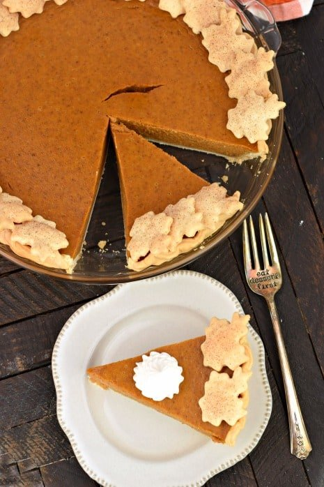 Pumpkin pie slice on a white plate with a dollop of whipped cream, whole pie in background.