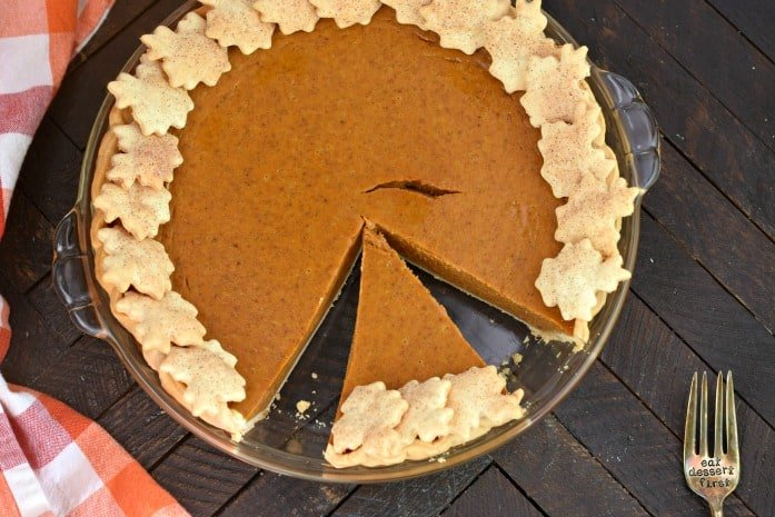 Whole pumpkin pie with one slice removed.
