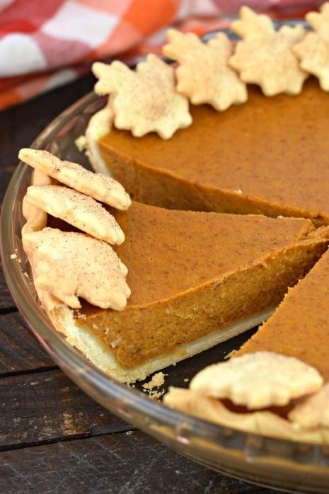 Pumpkin pie with one slice cut.