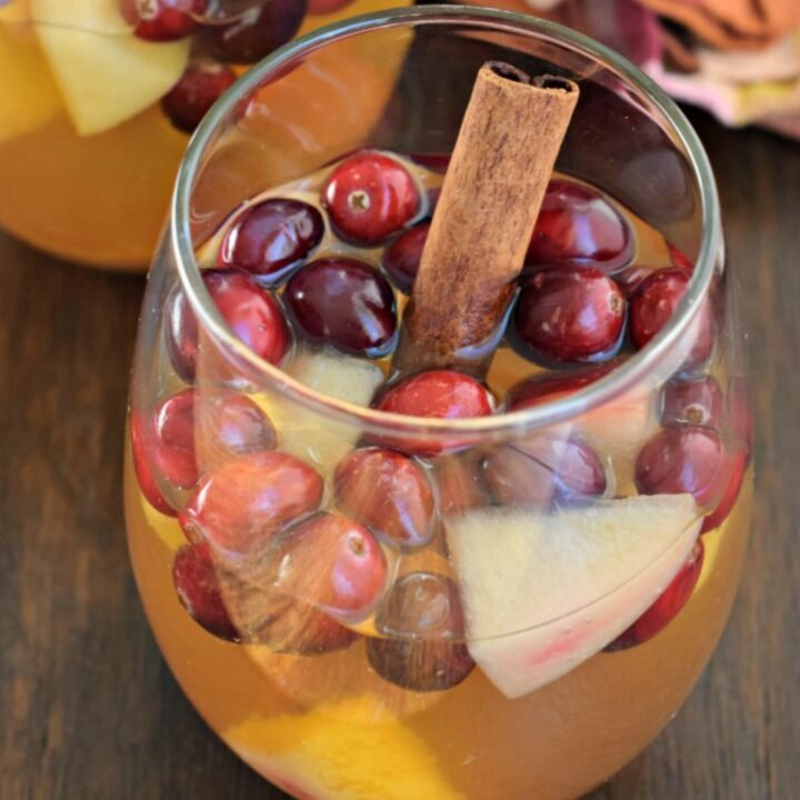 Apple cider sangria in clear glass with fruit and cinnamon.