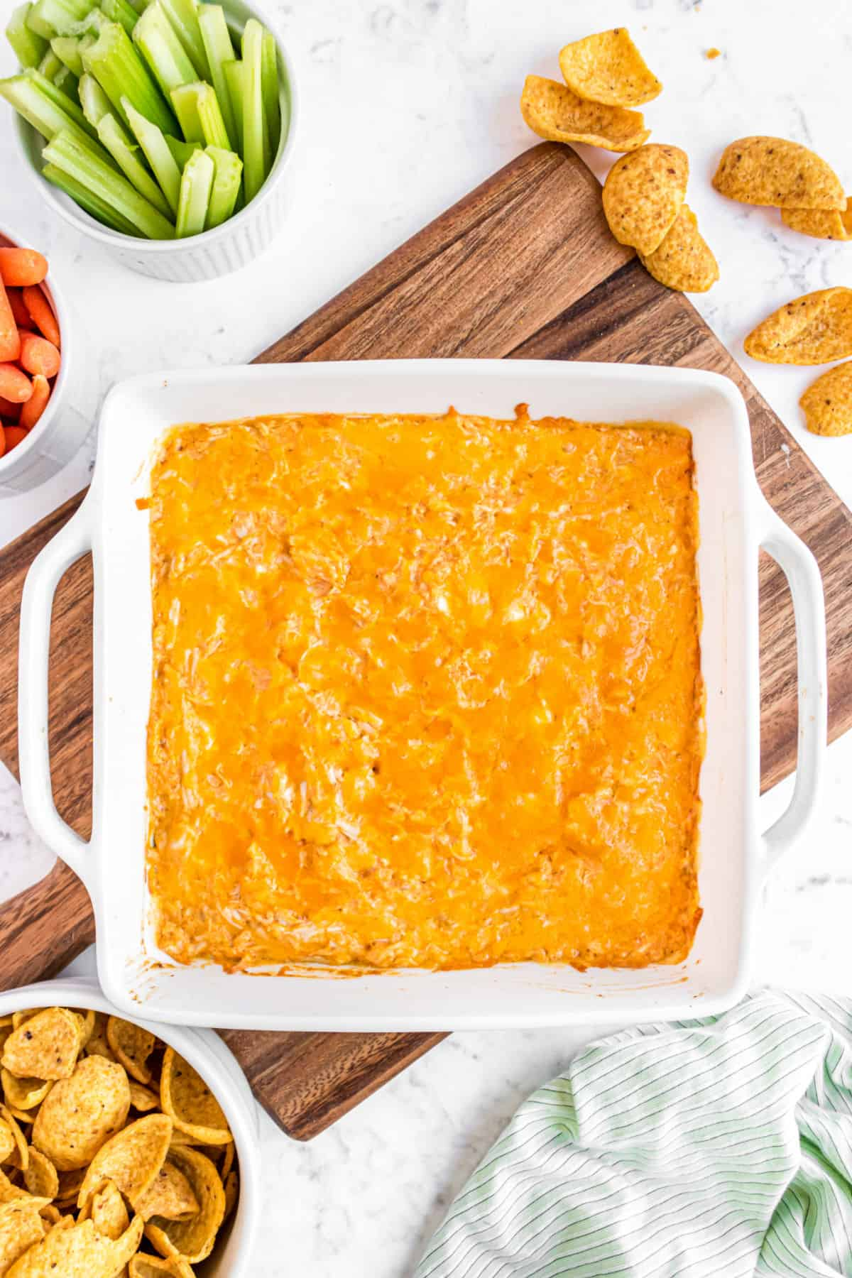 Baking dish with buffalo chicken dip and vegetables on the side.