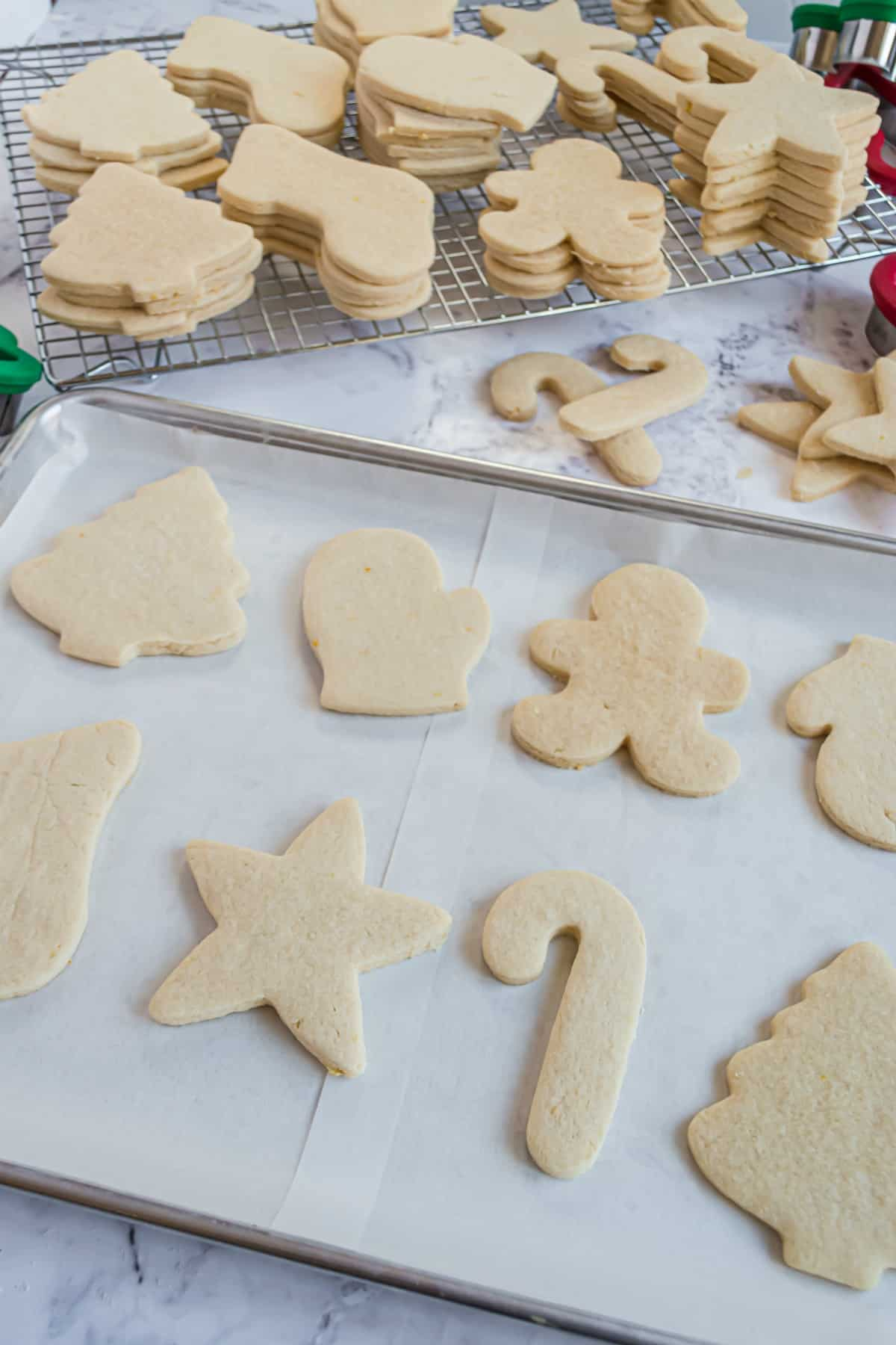 Unfrosted sugar cookies in christmas shapes on parchment paper and wire rack.