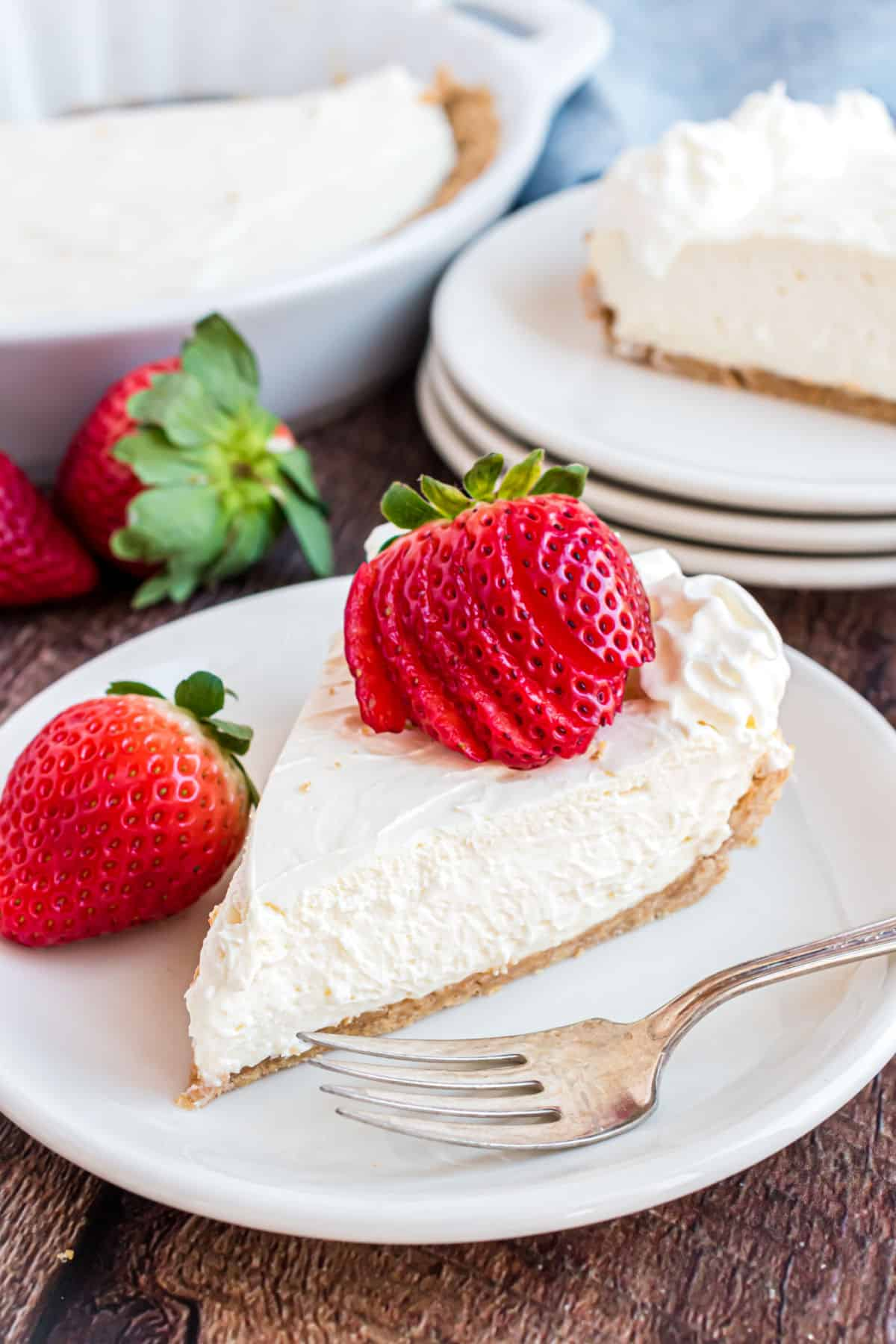 Slice of cheesecake with fresh strawberry and whipped cream.