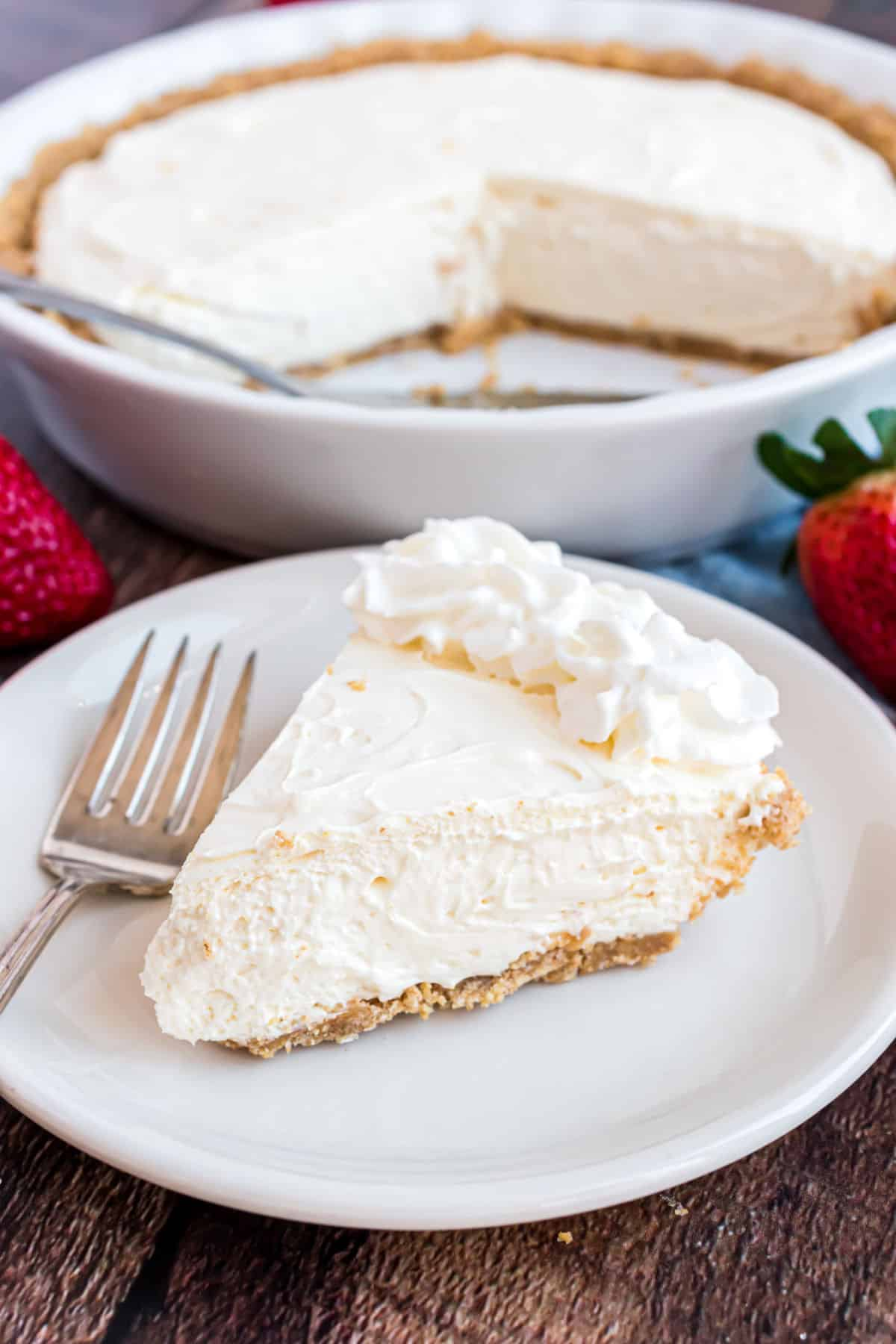No bake cheesecake sliced and garnished with whipped cream.