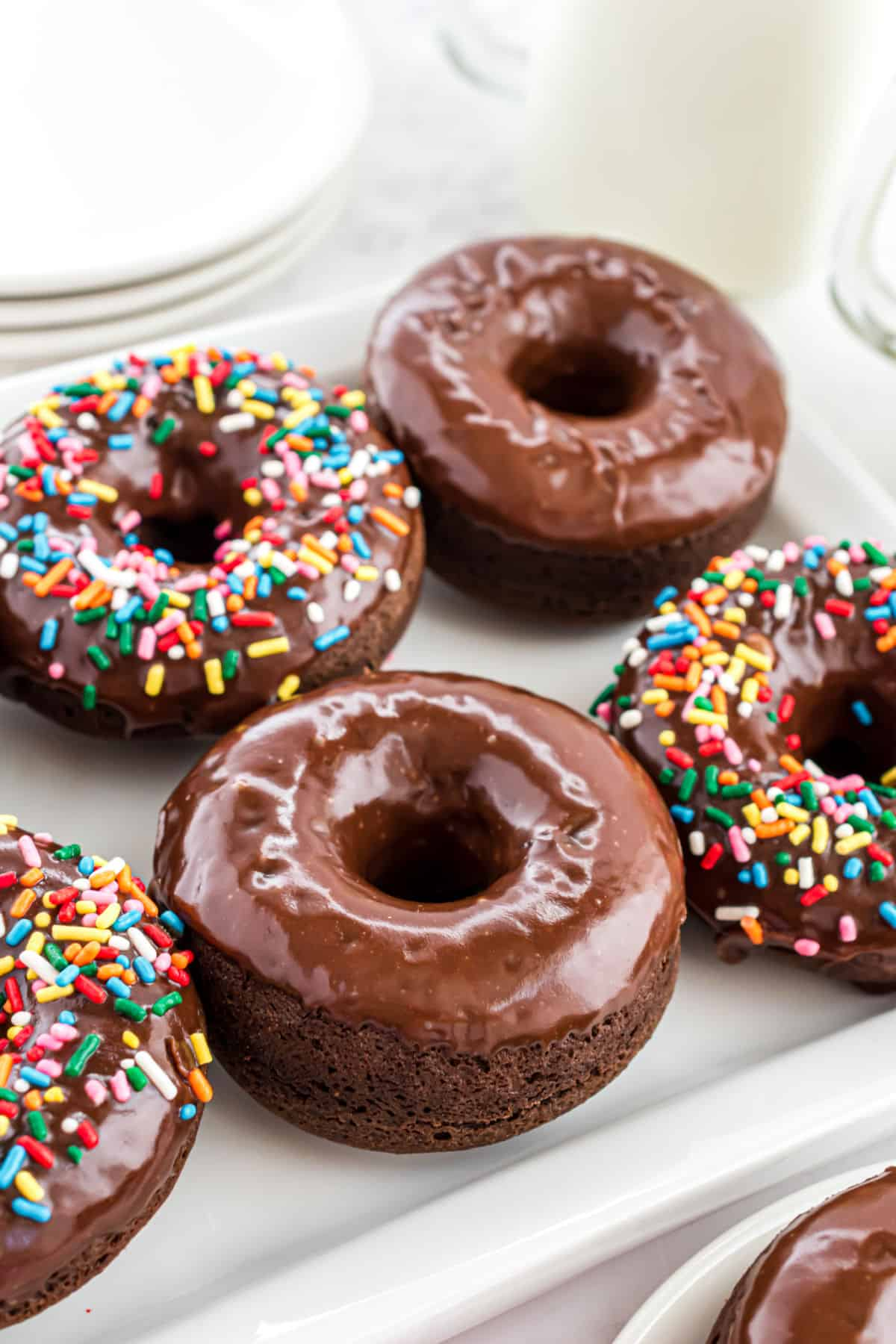 Chocolate glazed donuts on a white plate.