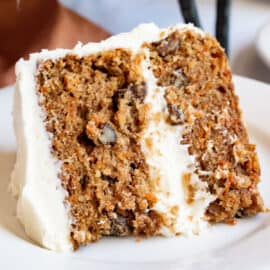 Slice of carrot cake with cream cheese frosting on white plate.