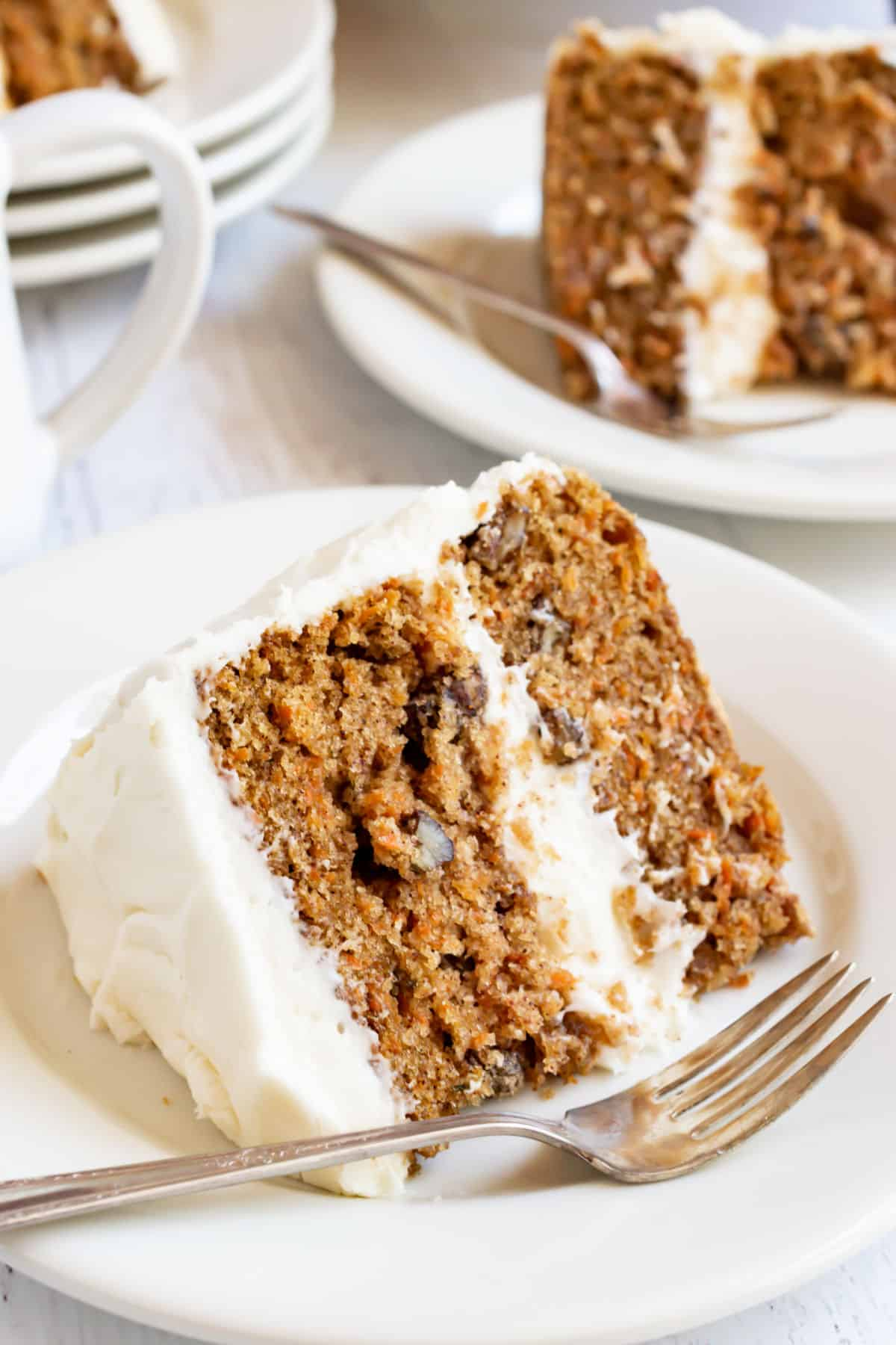 Two slices of carrot cake with cream cheese frosting on white plates.