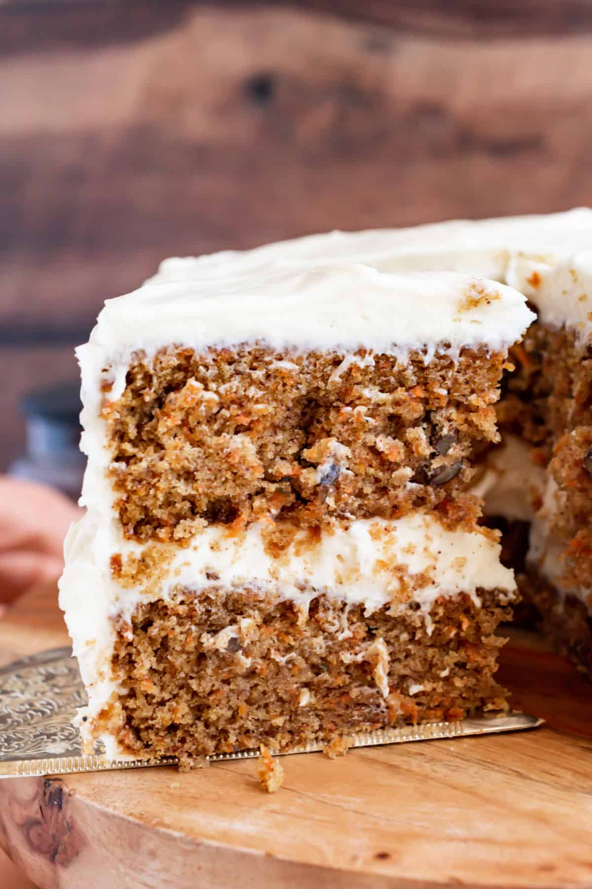 Double layer carrot cake with cream cheese frosting on a wood cake platter.