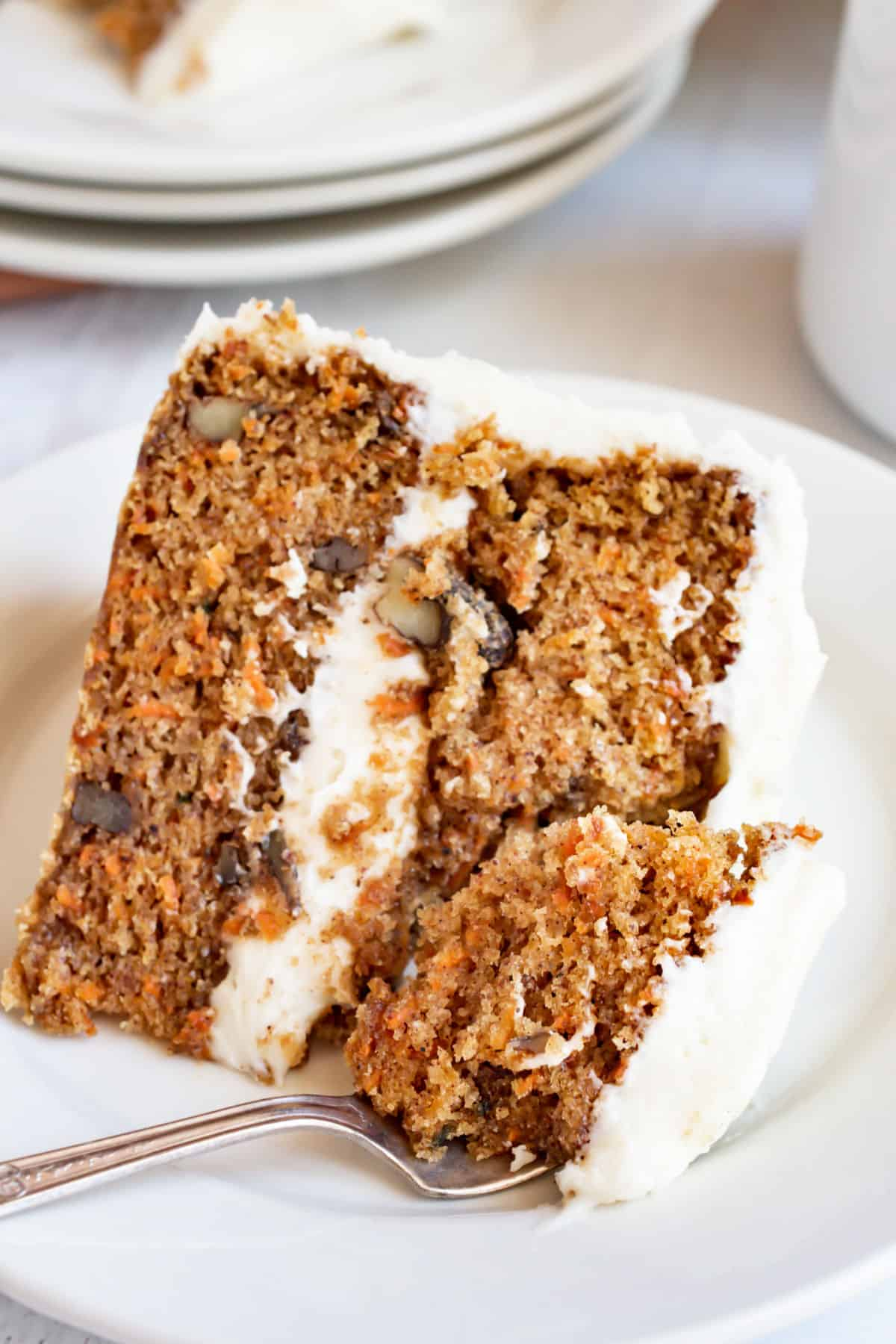 Slice of carrot layer cake on a plate with a fork.