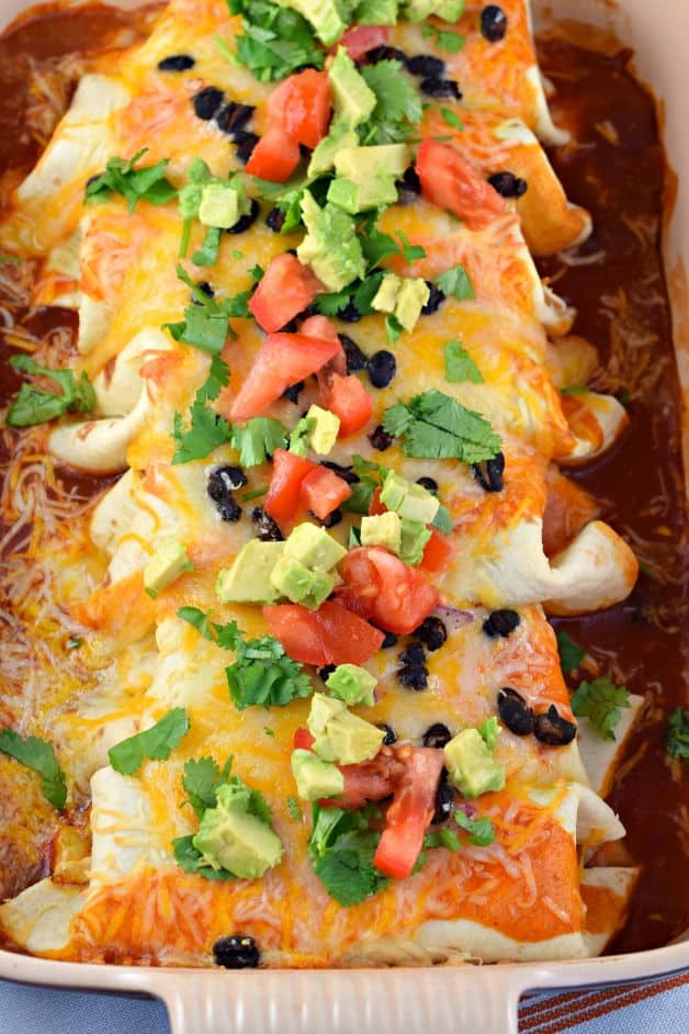 Chicken enchiladas stuffed with avocado and beans and topped with fresh vegetables.