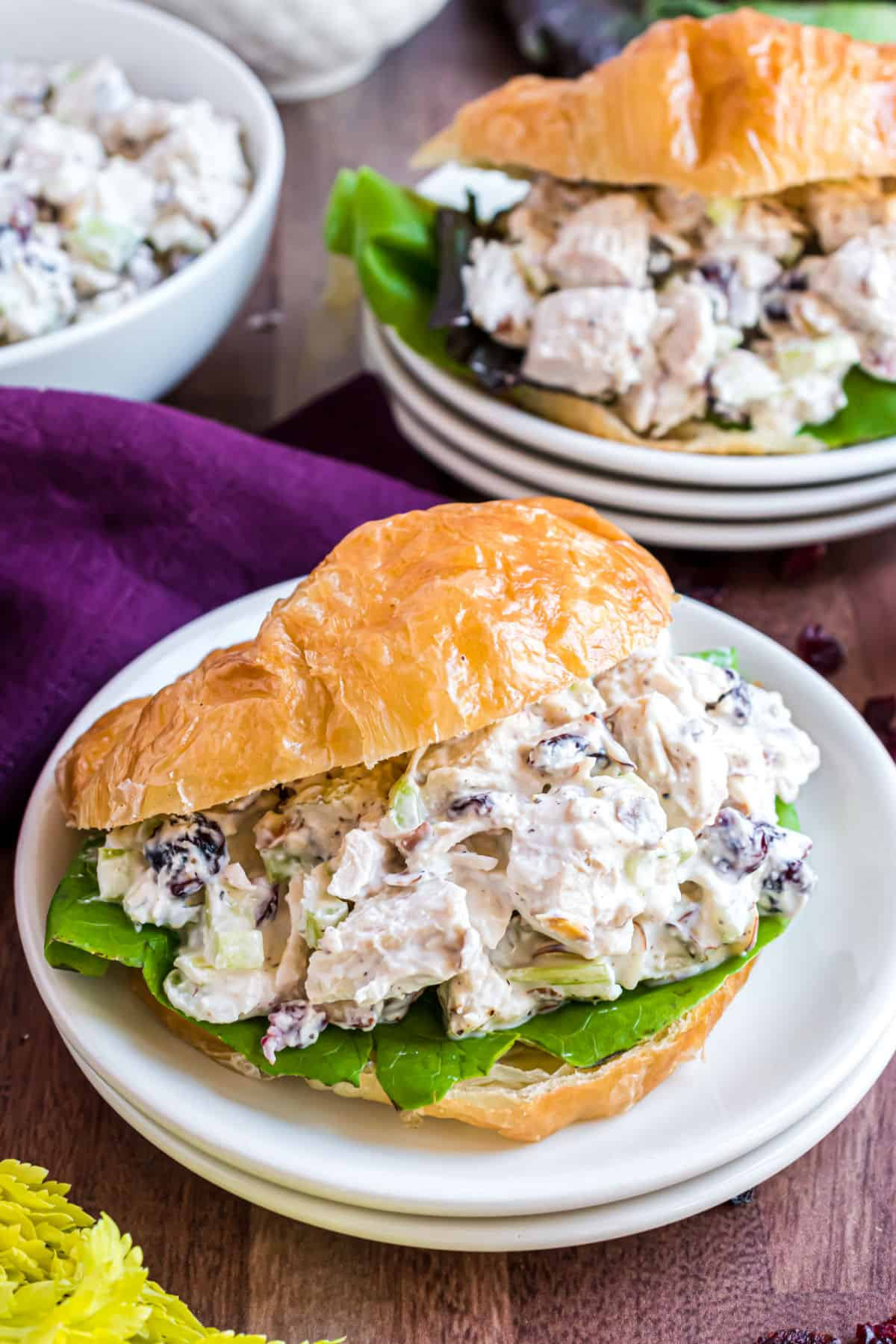 Chicken salad on a croissant with a bed of lettuce.