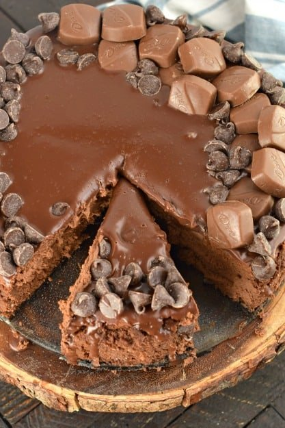 Whole chocolate cheesecake with one slice cut.