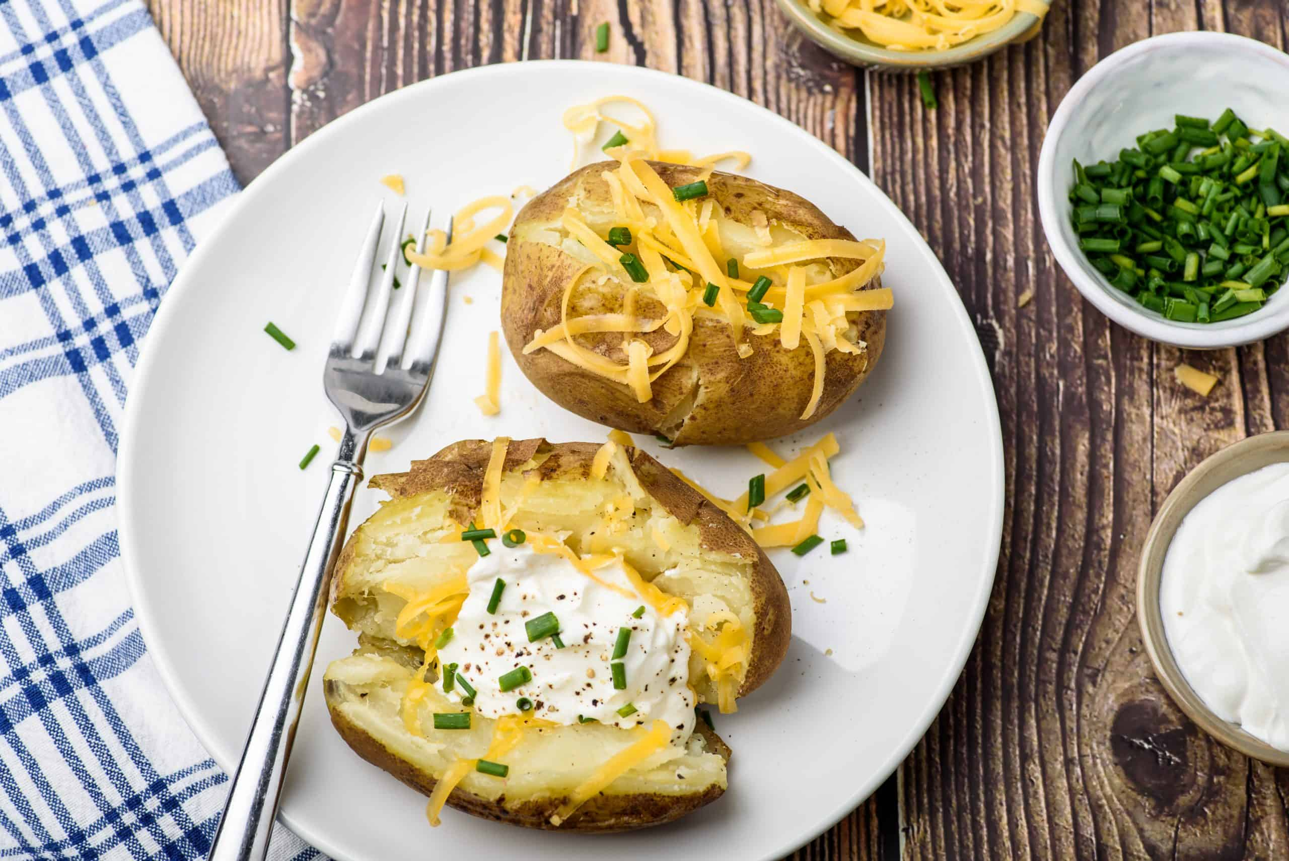 Dinner plate with baked potatoes topped with cheese and sour cream.