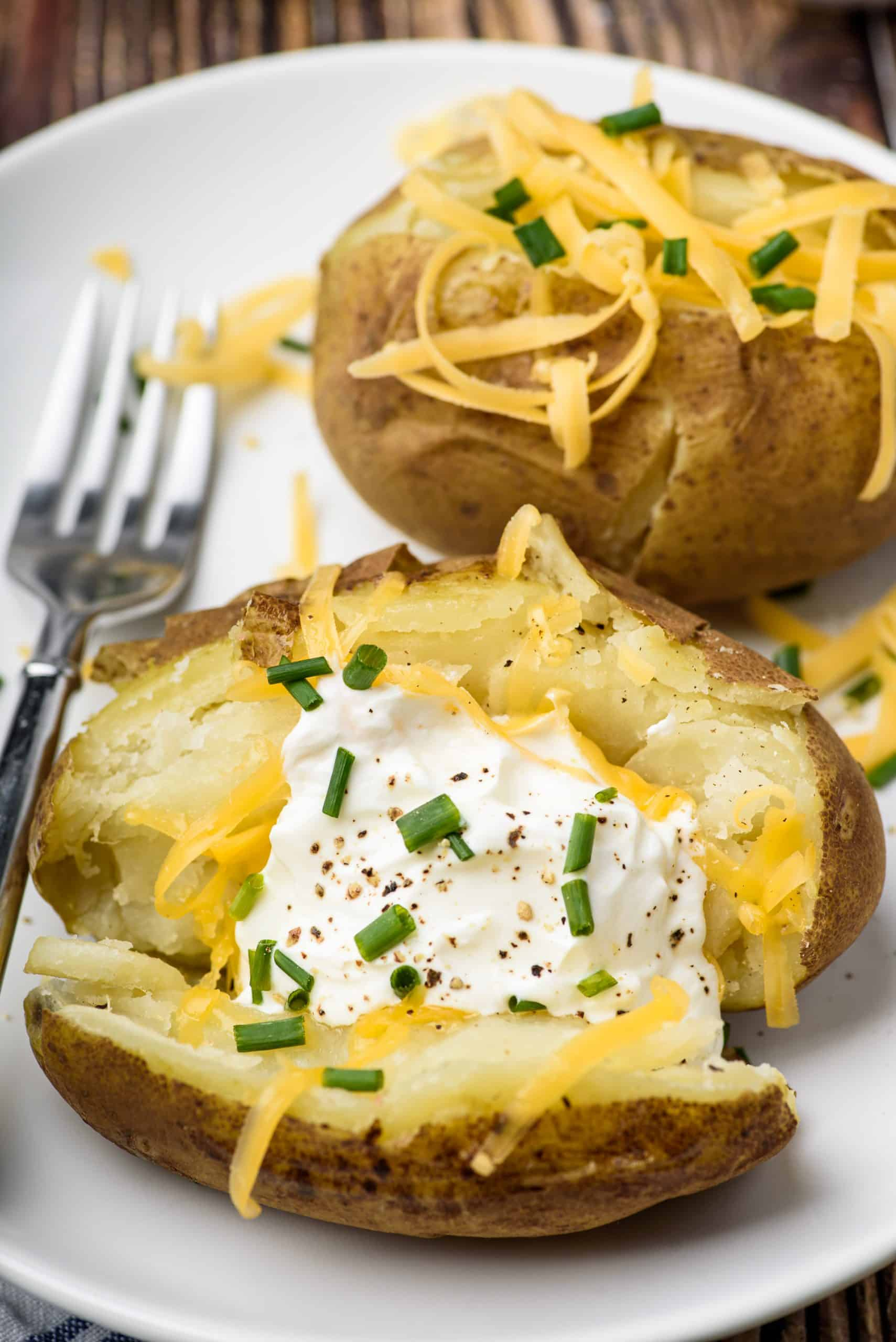 Baked potatoes open in half and topped with sour cream, cheese, and chives.