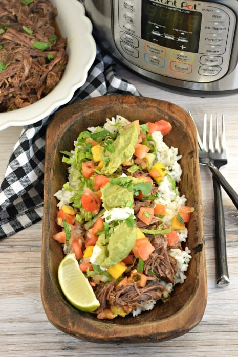 Wooden bowl with cilantro lime rice, beef barbacoa, guacamole, mango salsa, lime, and sour cream. Made in the instant pot.