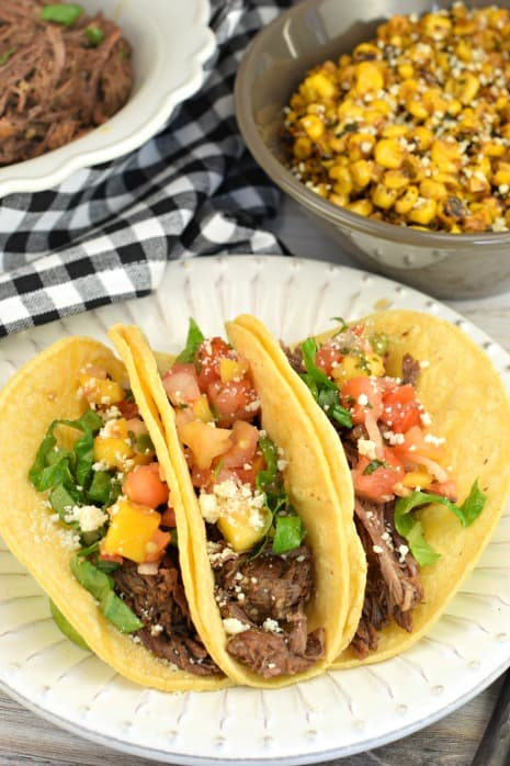 Three corn tortillas with instant pot beef barbacoa filling. Topped with mango salsa, lettuce, cotija cheese, and served with mexican corn.