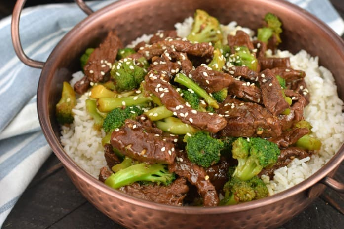 Copped skillet with white rice and beef broccoli garnished with sesame seeds.