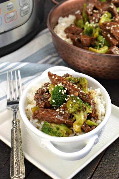 White bowl with rice topped with beef broccoli.