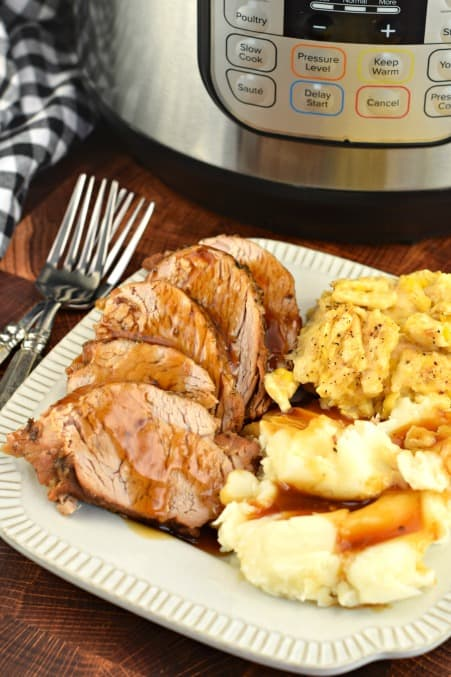 Dinner plate with sliced pork tenderloin, mashed potatoes, and corn casserole.
