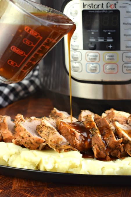 Balsamic glaze being poured over sliced pork tenderloin.