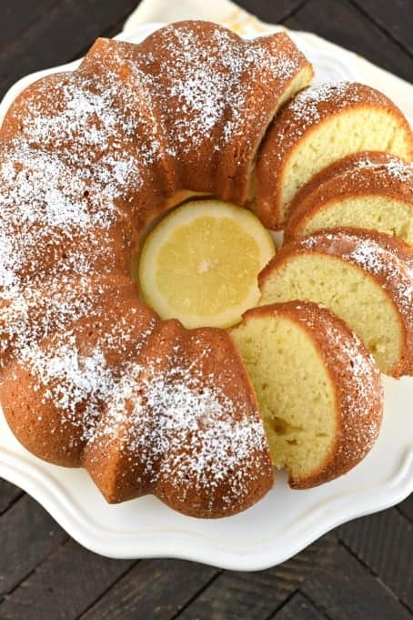 Italian Lemon Cream Bundt cake on a white plate. Sliced and dusted with powdered sugar.