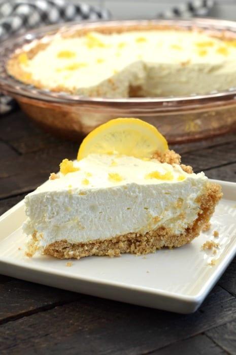 Slice of lemon cheesecake with graham cracker crust on a white square dessert plate.