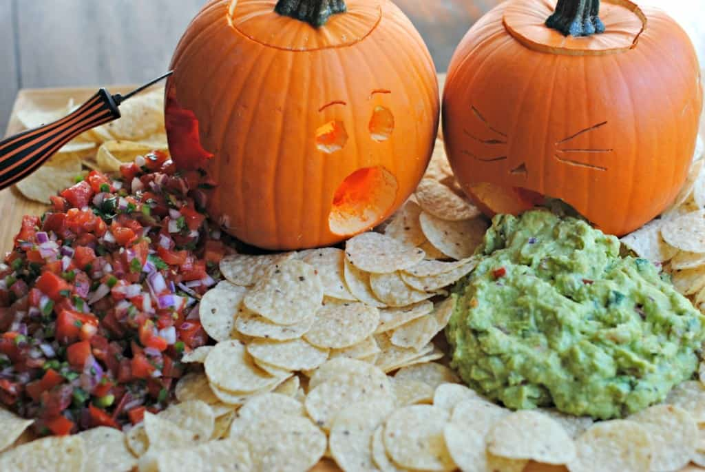 Two pumpkins carved and served with guacamole and pico de gallo.