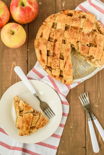 Apple Pie with lattice top. One slice served on a white plate with white fork.