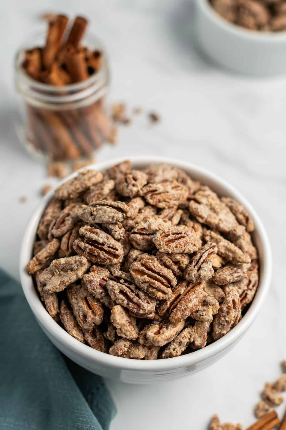 White bowl filled with candied pecans. Cinnamon sticks in background.