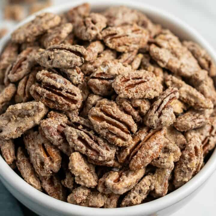 Candied pecan halves in a white bowl.