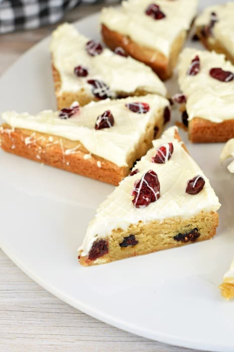 White round plate with several triangle slices of cranberry bliss bars. Each bar is topped with frosting and white chocolate drizzle.